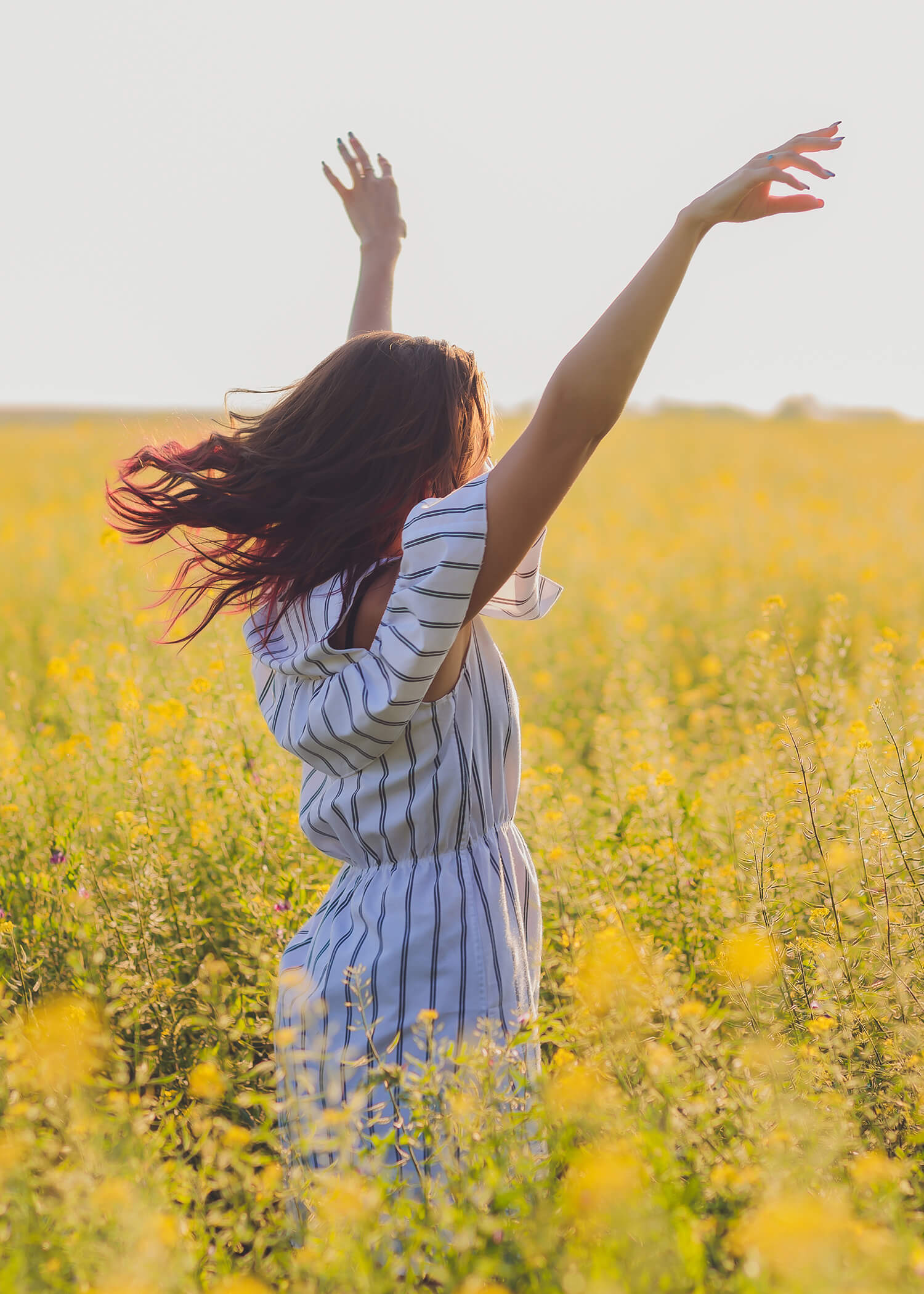 Image of woman in field of yellow flowers. This image illustrates the support people can get for loneliness in Los Angeles, CA when using a comprehensive DBT program in Torrance, CA. 90254 | 90266