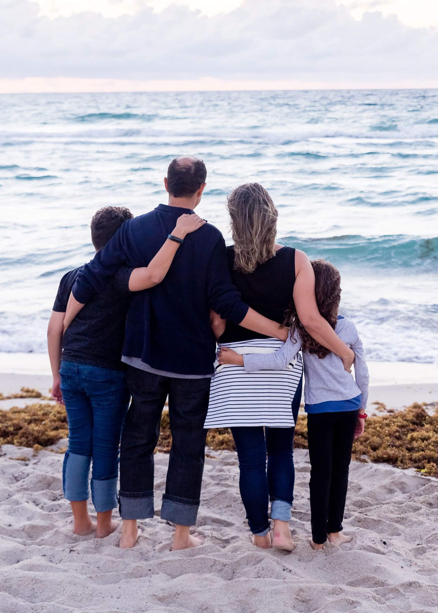 Image of a family of four looking out at the ocean together. A DBT therapist in Los Angeles, CA can help teens and families forms healthy family dynamics in Torrance, CA. 90254 | 90266