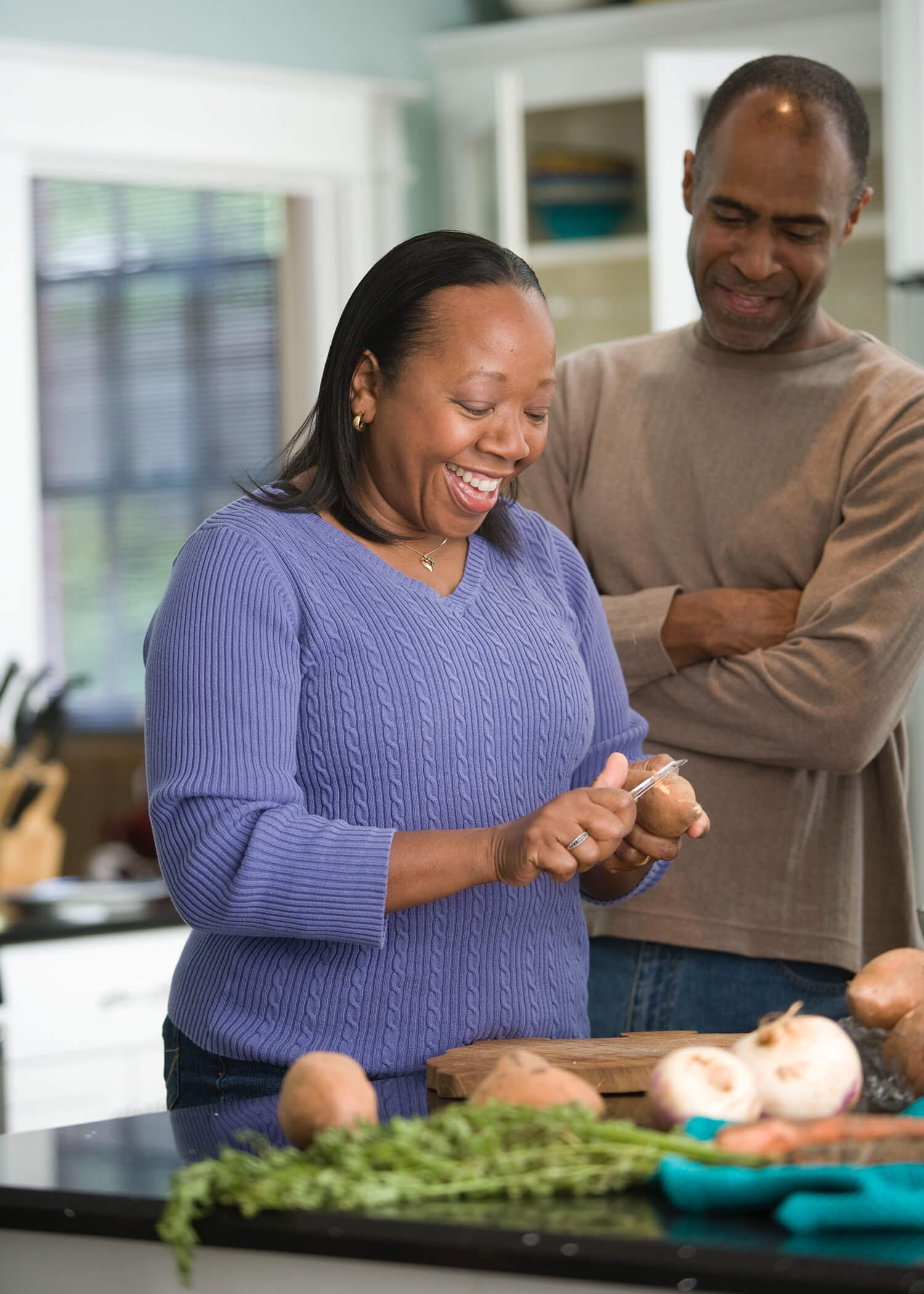 Image of a woman peeling potatoes in the kitchen with her husband next to her. This image represents how you can find joy again after doing the DBT program in Los Angeles, CA. 90266   90505