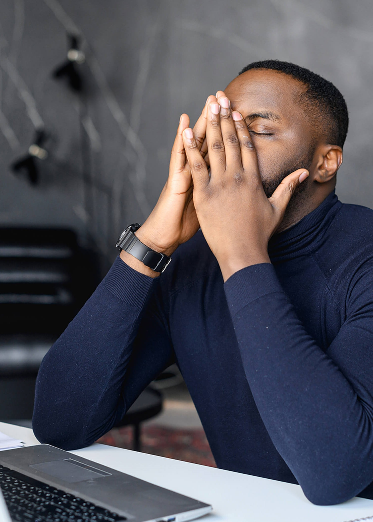 Image of a man sitting at a desk with his hands held to his face in frustration. If you are struggling with managing anger in Los Angeles, CA, reach out to a DBT therapist. | 90277 | 90254