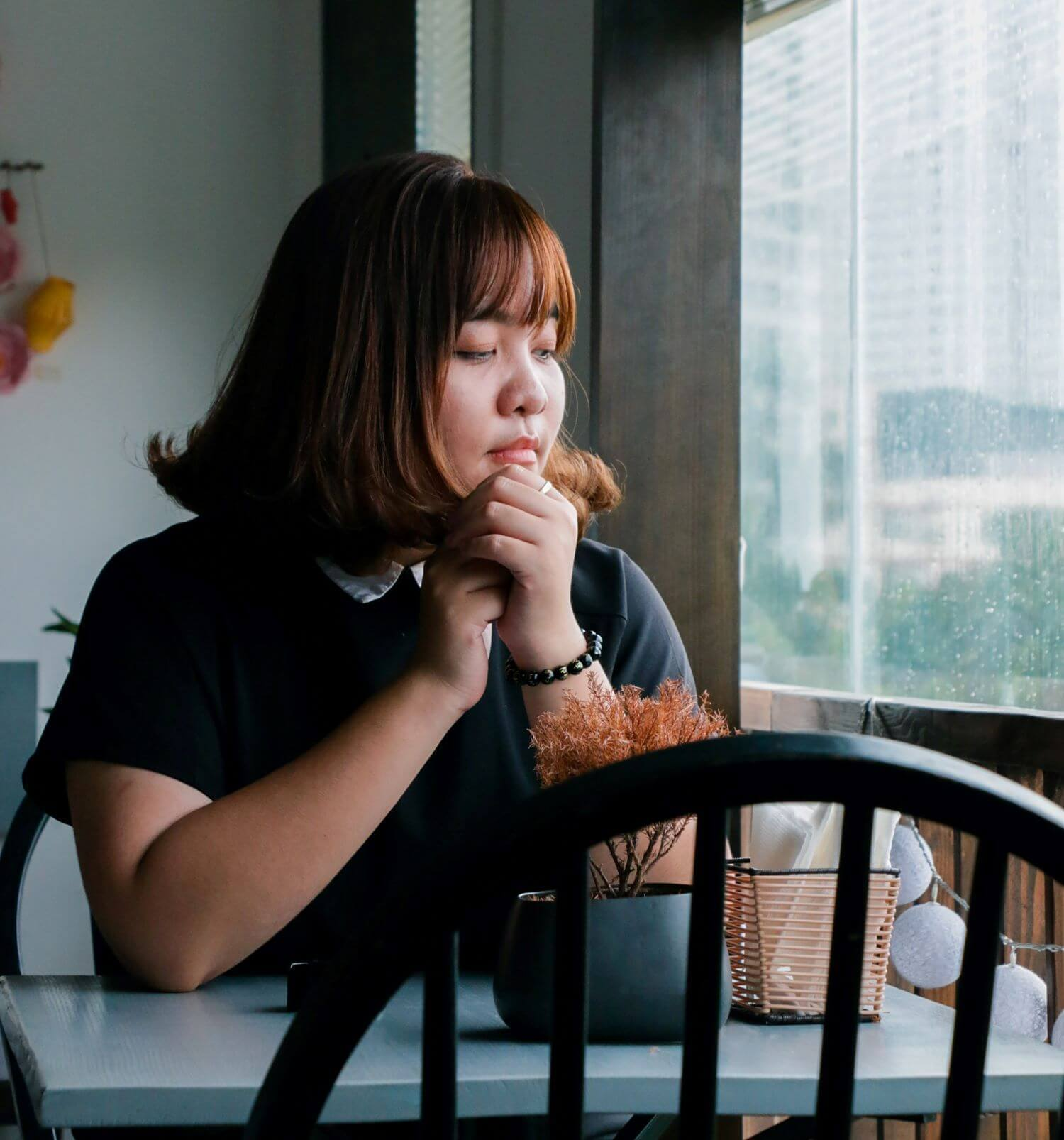 Image of a woman sitting alone in a cafe looking outside. This image illustrates how lonely people with anger issues in Torrance, CA can feel. If you are interested in learning about managing anger in Torrance, CA, reach out to us. | 90266 | 90505