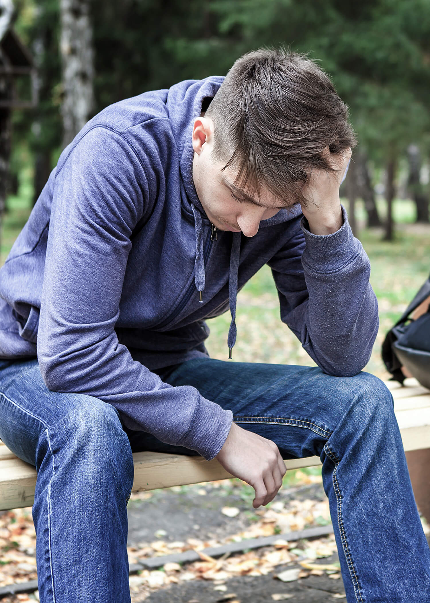 Image of a young man sitting on a bench with his hand running through his hair. This image illustrates the loneliness that dealing with suicidal thoughts can bring. Meeting with a DBT therapist to reduce suicidal thoughts in Los Angeles, CA can help. | 90266 | 90505