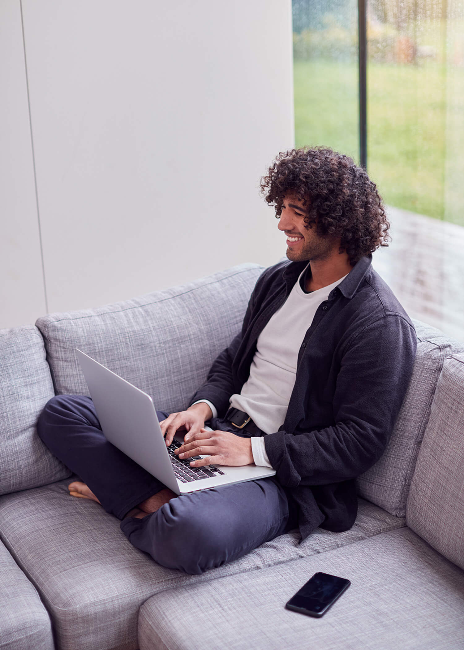 Image of a man sitting on a couch using a laptop and smiling. This image represents what it could look like for you to meet with an online DBT therapist in California. The DBT Center uses online therapy in California to serve people in need of online DBT therapy in California. | 90277 | 90254