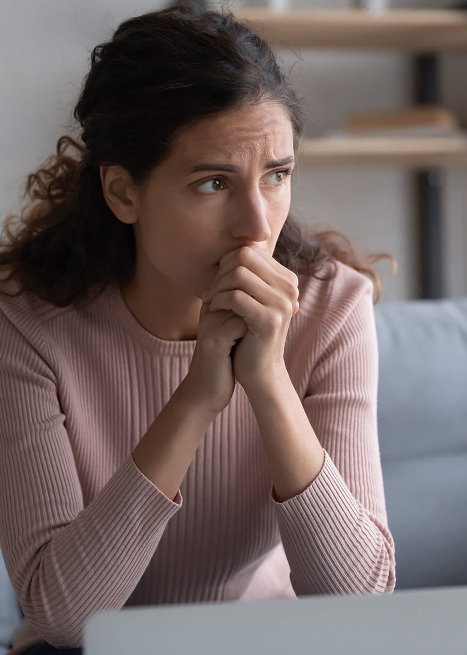 Image of a woman wearing a pink sweater holding her hands to her mouth and looking nervous. This image illustrates how someone engaging in self-harm may feel. Those struggling with self-harm in Los Angeles, CA can get support from a DBT therapist. | 90274 | 90275