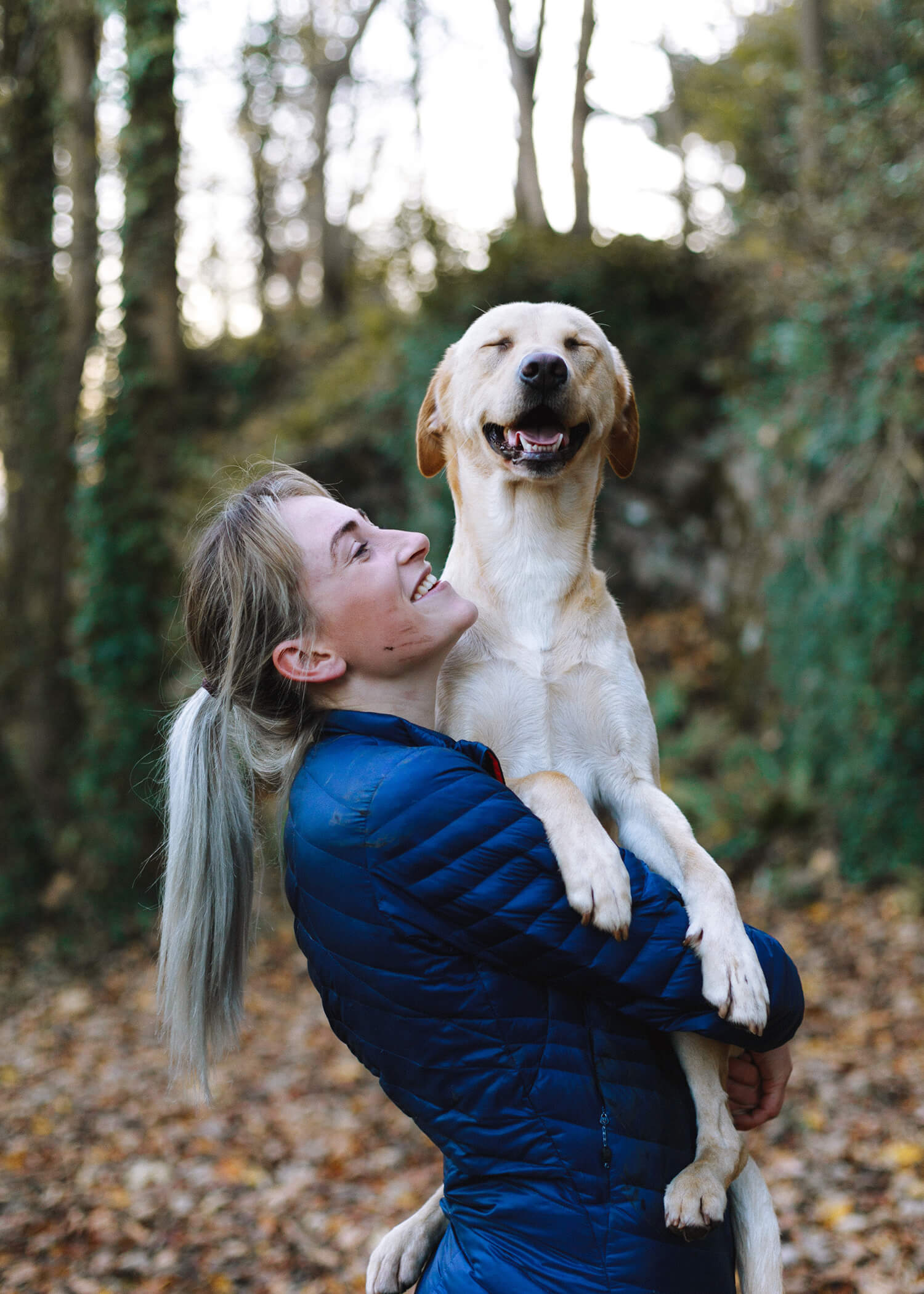 Image of a woman holding a dog and smiling. This image demonstrates what someone who previously used self-harm may look like after DBT. A DBT therapist can help you learn about managing self-harm in Los Angeles, CA. | 90266 | 90505