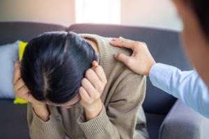 Image of a person with their head down and a hand on their should offering support. This image illustrates how a DBT therapist can help people struggling with self-harm in Los Angeles, CA. 90274   90275