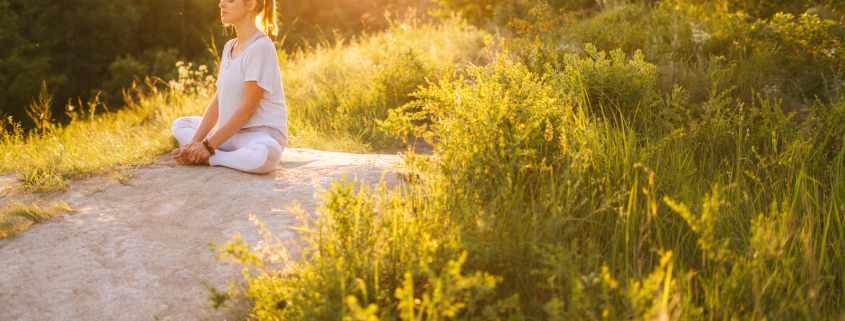 Image of a woman sitting on a rock peacefully. This image represents mindfulness skills, which a DBT therapist can teach for those using self-harm in Los Angeles, CA. 90277   90254