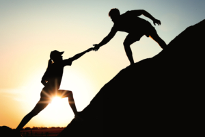 Image of a person extending their hand to help another person climb up a rock. This image depicts how a DBT therapist in Los Angeles, CA can help a person struggling with self-harm.   90266   90505