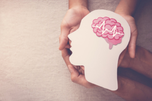 Person holding white head cutout with pikn brain and a wavelength on brain. You may be tired of the emotional distress you're struugle with. Trauma is hard. Learn how DBT PE in Los Angeles and Las Vegas can help you. Additionally, learn about what is dialectical behavioral therapy today!